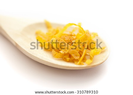 Fresh lemon zest on a wooden spoon, on white background