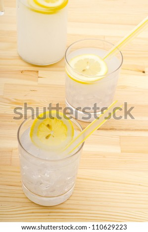 fresh lemonade drink with lemon slice closeup and pitcher carafe over pinewood table