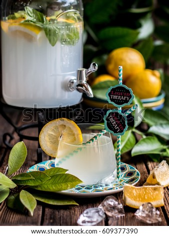 Fresh lemonade in a big jug with ice, mint and lemon slices