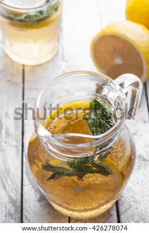 Fresh lemonade in a glass jug on a white background - stock photo