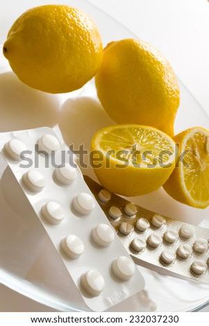 fresh lemons and flu pills in blister- home grippe remedy - stock photo