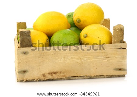 fresh lemons and lime fruits in a wooden box on a white background