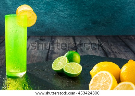 Fresh lemons and limes freshly cut with colored glass - stock photo