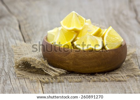 fresh lemons in a bowl on wooden background - stock photo