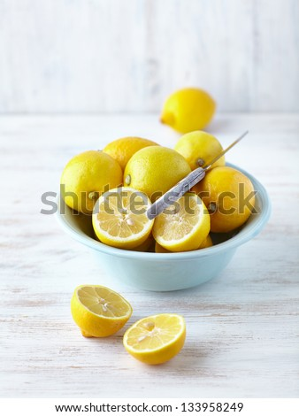 Fresh lemons in a bowl; whole and halved