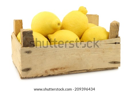 fresh lemons in a wooden crate on a white background - stock photo