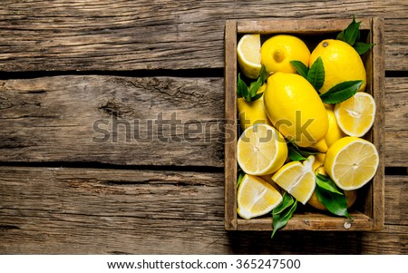 Fresh lemons in an old box with leaves. On wooden background. Free space for text . Top view - stock photo