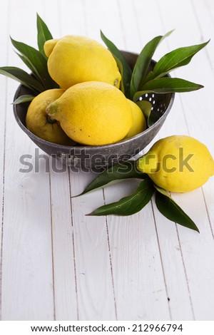 Fresh lemons in bowl on white wooden background. Selective focus, vertical. - stock photo