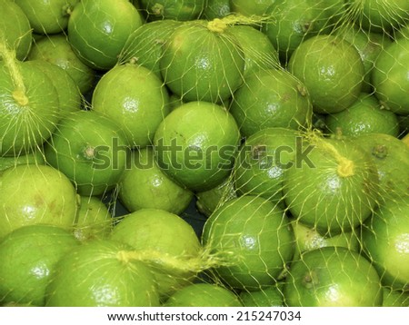 Fresh lemons in plastic netting In Market. Food background texture - stock photo