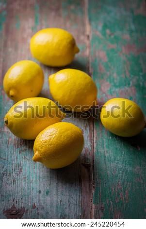 Fresh lemons on aged wooden background. Selective focus. - stock photo