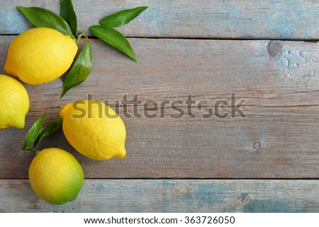 Fresh lemons on wooden background with copy space - stock photo