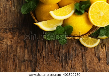 Fresh lemons with green leaves in bowl on wooden table, top view - stock photo