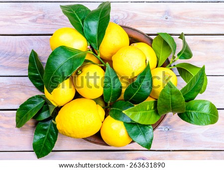 Fresh lemons with leaves in plate on rustic wood table.Citrus fruit. - stock photo