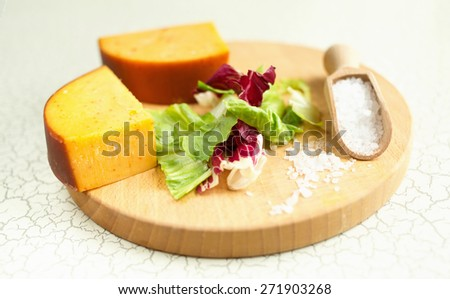 Fresh lettuce, cheese, ham and sea salt on a cutting board. Intercontinental breakfast at the hotel.