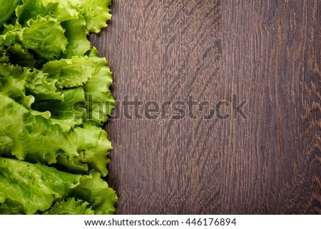 Fresh lettuce leaves on a dark wood background. Top view. Free space for text. - stock photo