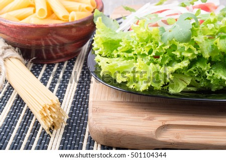 Fresh lettuce on a plate close-up, paste in a small bowl and a bunch of spaghetti on the table with a dark striped background