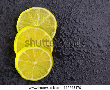 Fresh lima slices with water drops on black slate stone background - stock photo