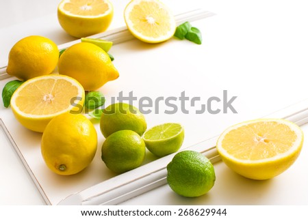 Fresh lime and lemon citrus fruits on white background. Copy paste your own text. Empty space next to yellow and green juicy fresh fruits on white bakground.