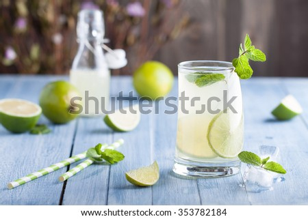 Fresh lime and lemon lemonade with mint in a glass on a blue wooden desk - stock photo