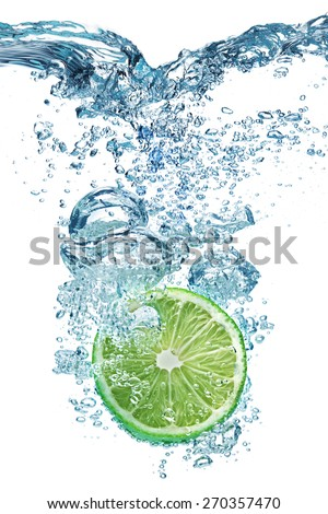 Fresh lime dropped into water with splash isolated on white - stock photo