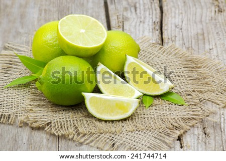 fresh lime fruits on wooden background - stock photo