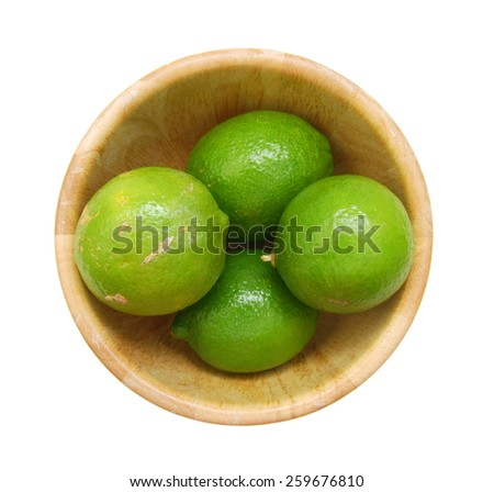 Fresh lime green in wooden bowl on a white background.