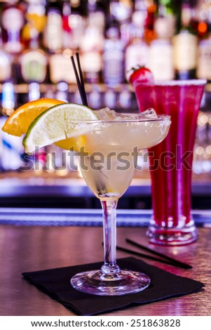 Fresh lime margarita with ice cubes in margarita glass sitting on bar top garnished with orange and lime wedges with strawberry vodka drink in background - stock photo