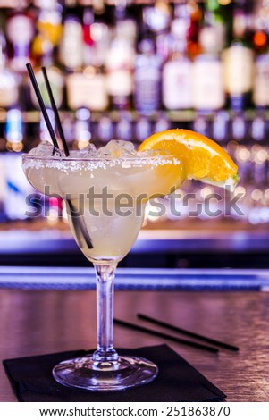 Fresh lime margarita with ice cubes in margarita glass sitting on bar top garnished with orange and lime wedges - stock photo