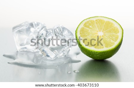 Fresh lime with melting ice cubes on metallic surface