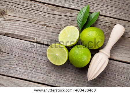 Fresh limes and juicer on wooden table. Top view with copy space - stock photo