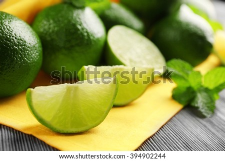 Fresh limes and mint on yellow napkin - stock photo