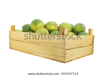 Fresh limes in wooden box isolated on white background