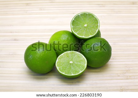 Fresh limes on bamboo background. Image of natural materials. Eco style.  - stock photo