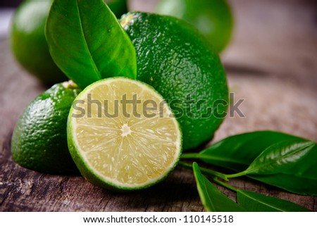 Fresh limes on wooden background - stock photo