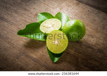 Fresh limes on wooden plan background,split toning color effect - stock photo