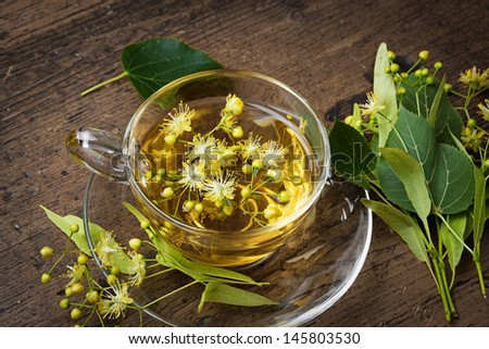 fresh linden tea on a wooden table - stock photo