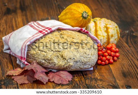 Fresh loaf of pumpkin bread wrapped in a towel - stock photo