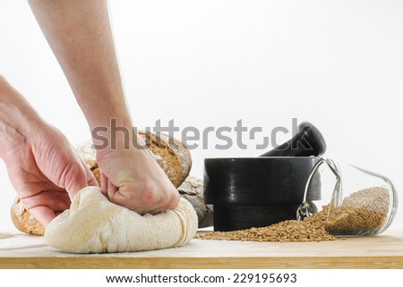 Fresh loaf of whole wheat sourdough bread dough being kneaded by a baker on a cuttingboard