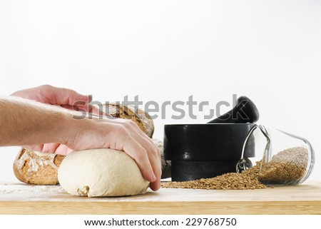 Fresh loaf of whole wheat sourdough bread dough being kneaded by a baker on a cuttingboard - stock photo
