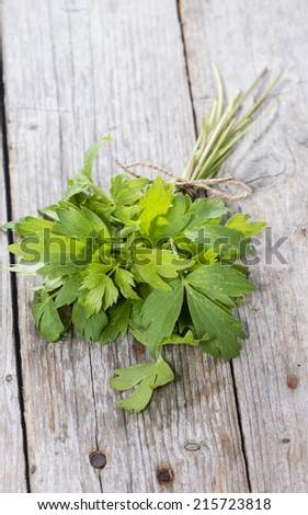 Fresh Lovage (detailed close-up shot) on wooden background