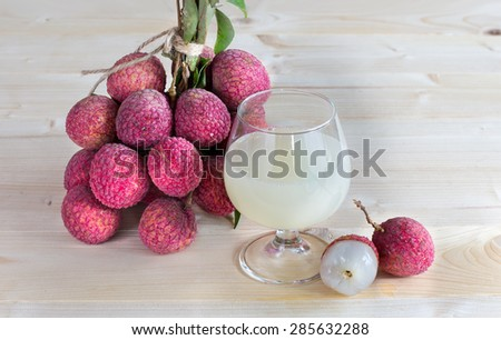 Fresh lychee juice in glass on wooden background - stock photo