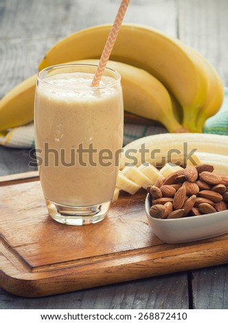 Fresh made Banana smoothie on wooden background - stock photo