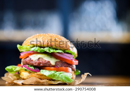 Fresh made cheeseburger with lettuce, tomato and onion.  - stock photo