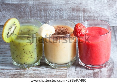 Fresh Made Chocolate Banana Smoothie, kiwi juice and strawberry juice on a wooden table. Selective focus. Milkshake. Protein diet. Healthy food concept.