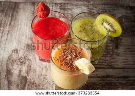 Fresh Made Chocolate Banana Smoothie, kiwi juice and strawberry juice on a wooden table. Selective focus. Milkshake. Protein diet. Healthy food concept. - stock photo