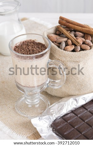 Fresh Made Chocolate Banana Smoothie on a wooden table with coffee and spices. Milkshake. Protein diet. Healthy food concept. Drink, cocoa beans, chocolate.