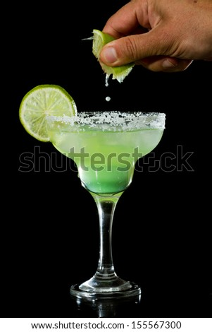 fresh made margarita isolated on a black background with a hand squeezing a lime over it - stock photo