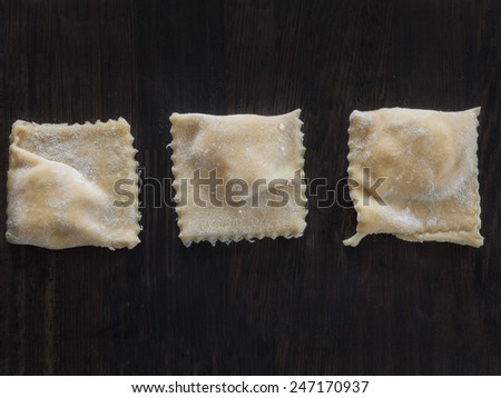 Fresh made ravioli with flour on a wooden board