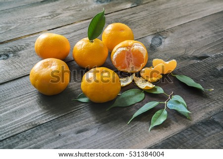 Fresh mandarines with leaves on wooden grey table