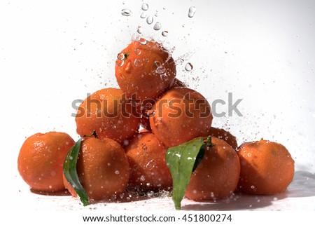 Fresh mandarins and splashing water. - stock photo